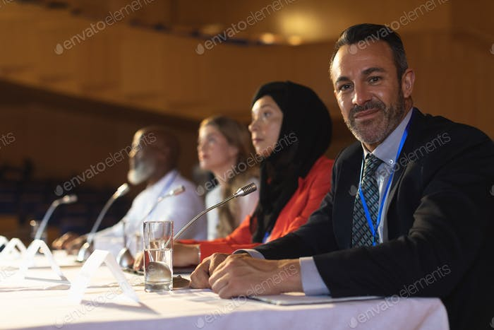 Businessman looking at camera while business colleague sitting together in the auditorium