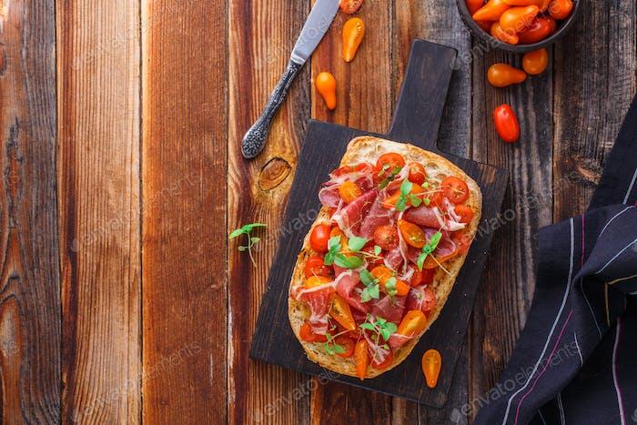 Italian antipasti - chiabatta with prosciutto, cherry tomatoes and basil.