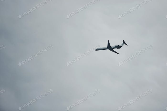 Passenger plane high up in the sky. Cloudy weather. Modern aviation