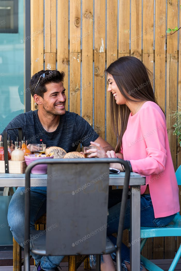 Happy young couple seating in a restaurant terrace eating a burg
