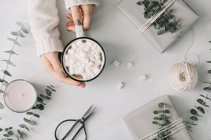Girl's hands hold a mug with hot chocolate and marshmallow