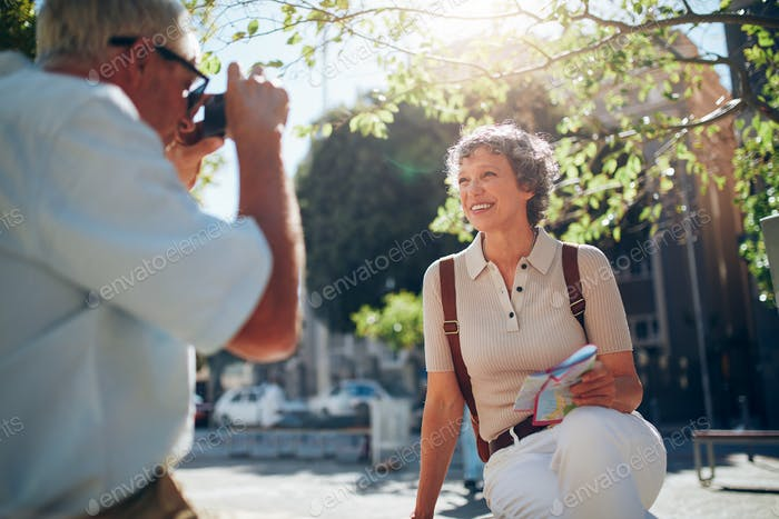 Senior man taking vacation photograph of his wife