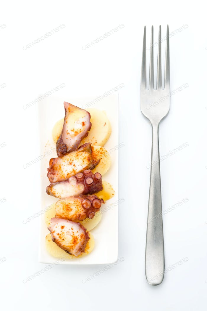 Marinated octopus sliced on potatoes isolated on white