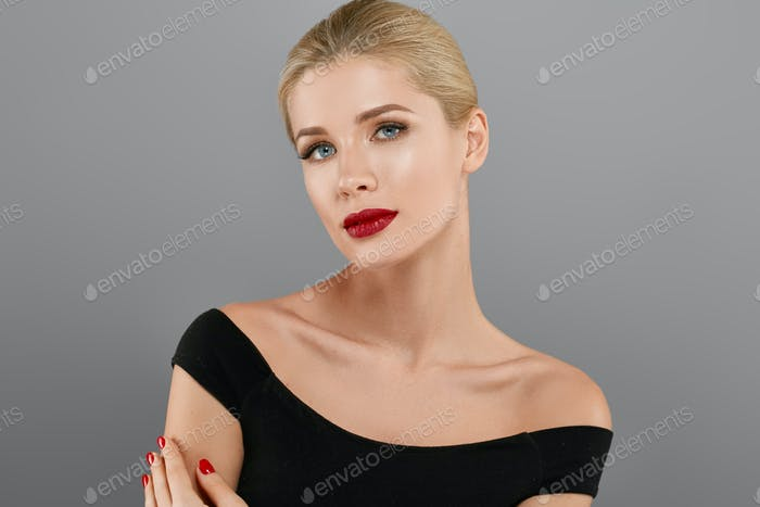 Blonde beautiful woman model over gray background. Woman nail manicure lipstick