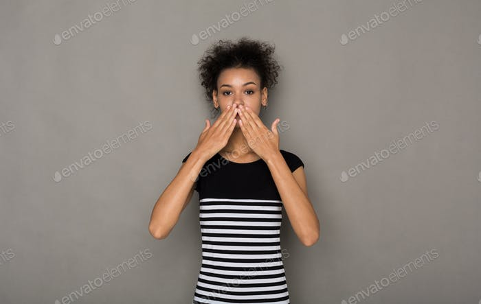 African-american woman covering mouth with hands