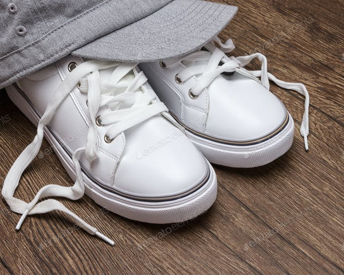 White sneakers with gray cap on dark wooden surface