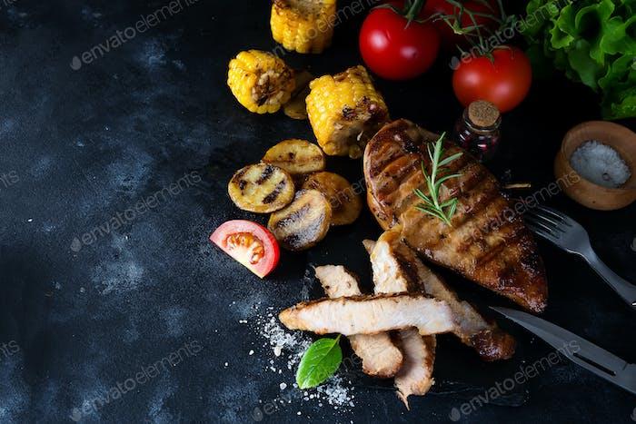 Gegrilltes Steak und Gemüse, gebackene Kartoffeln und grüner Salat auf dunkle