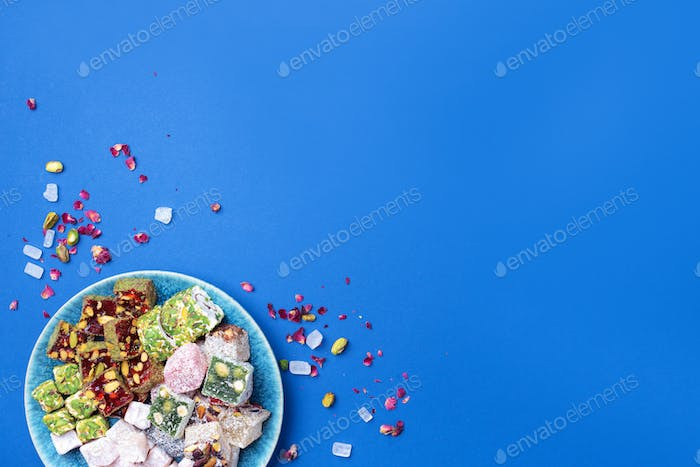 Middle Eastern sweets. Turkish delight with pistachios nuts on plate over blue background. Top view