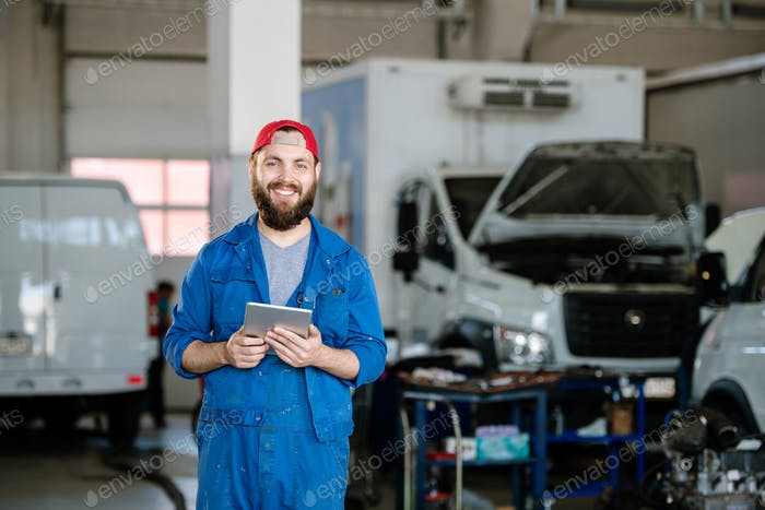 Young cheerful technician of machine repair service in workwear looking at you