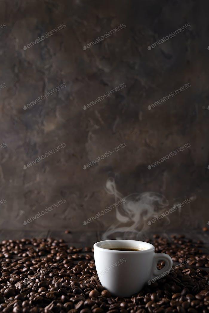 Tasse heißen Kaffee auf dem Hintergrund der Kaffeekörner auf einem dunklen Holzhintergrund, Kopierraum