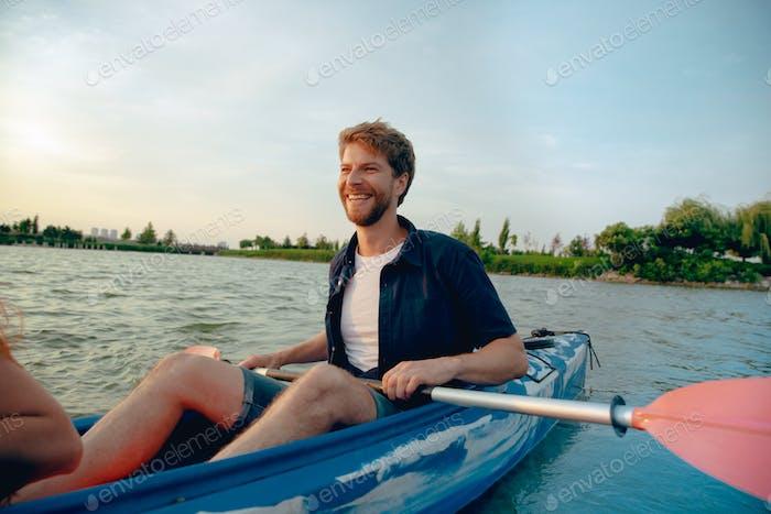 Уверенный молодой человек на каяках на реке с закатом на фоне