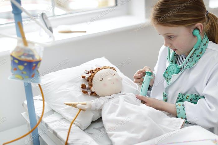 Junges Mädchen als Arzt gekleidet, der vorgibt, Patienten in Make-glauben Krankenhausbett zu behandeln