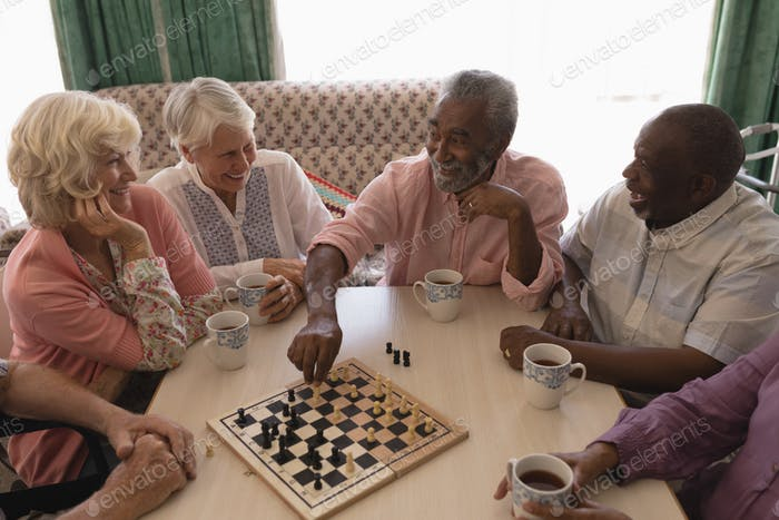 High angle view of group of senior people playing chess on table in living room at home
