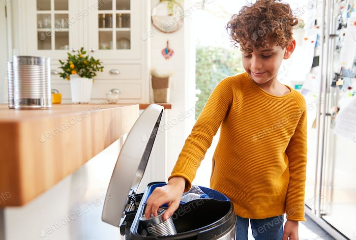 Boy Sorting Recycling Into Kitchen Bin At Home