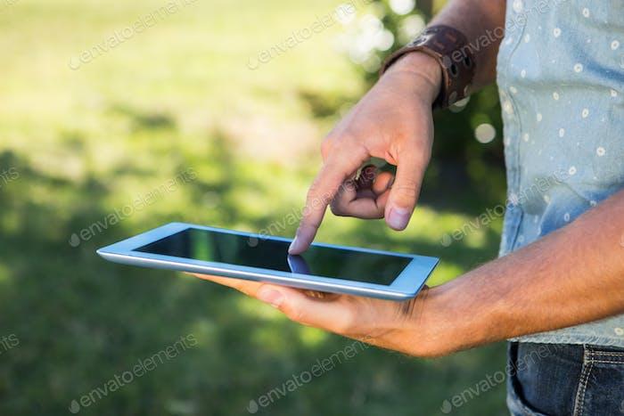 Junger Mann mit Tablet im Park an einem Sommertag