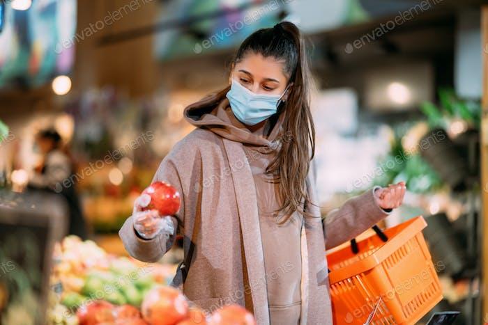 Mujer joven en máscara protectora hace compras