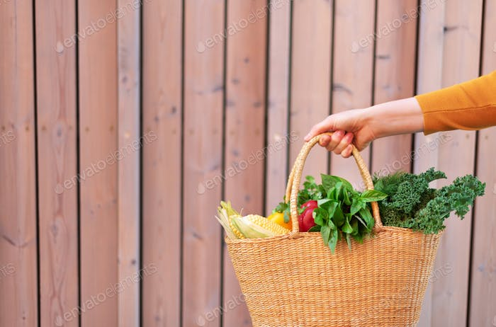 Woman hand holding straw basket with organic vegetables over wooden background. Healthy food