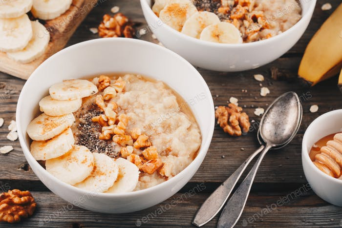 healthy breakfast bowl. oatmeal with banana, walnuts, chia seeds and honey