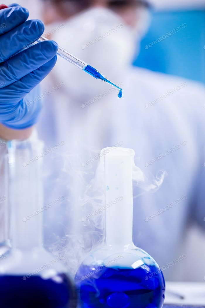 Closeup shot of blue solution dropping from a pipette
