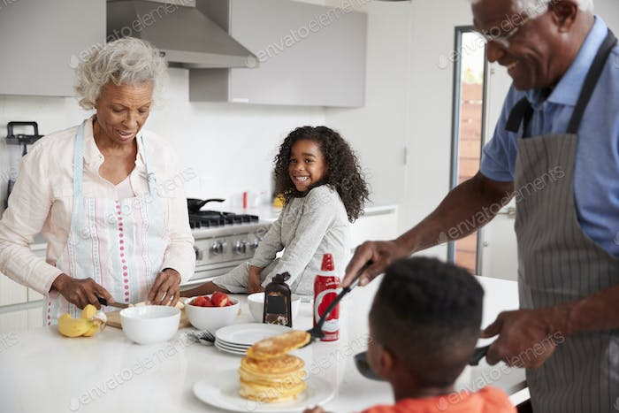 Grandparents In Kitchen With Grandchildren Making Pancakes Together