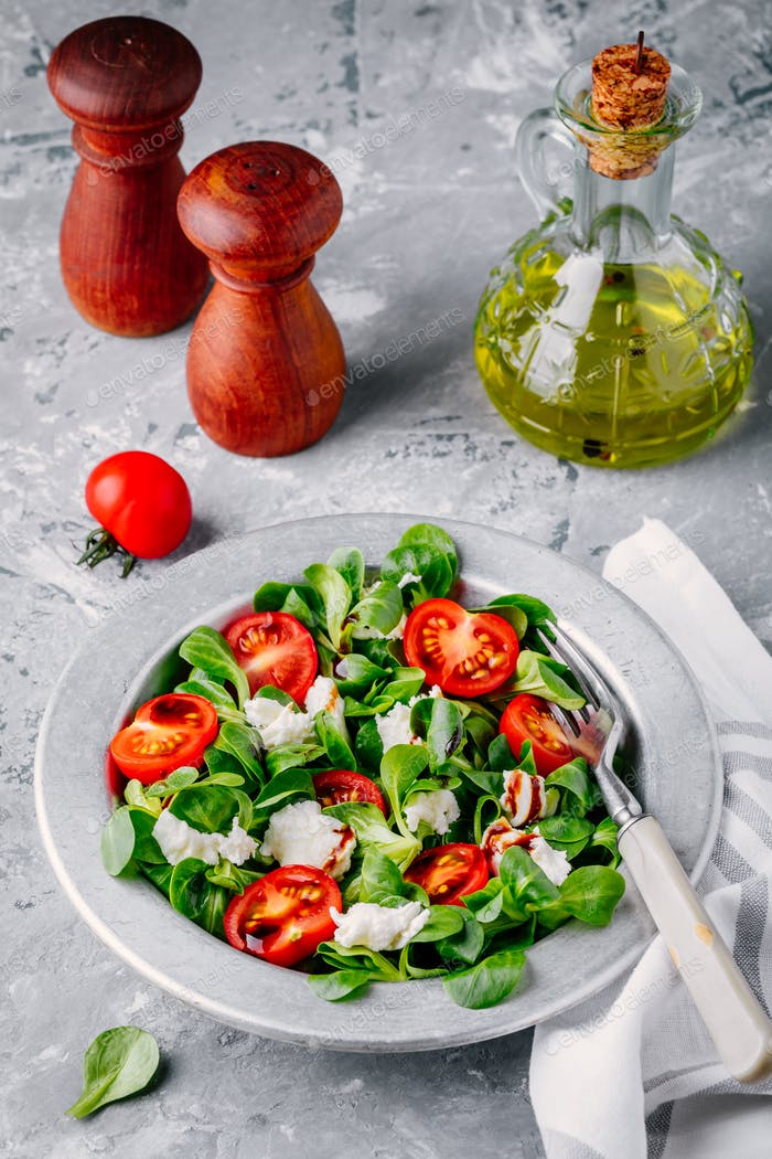 fresh salad bowl with green leaves, mozzarella, tomatoes and balsamic sauce