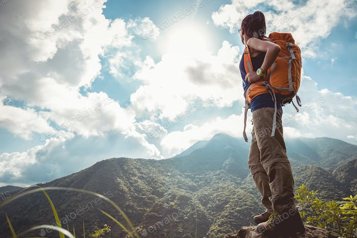 Successful woman hiker enjoy the view on sunrise mountain top
