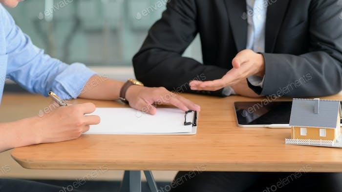 Клиент подписывает договор жилищного кредита с представителем банка.