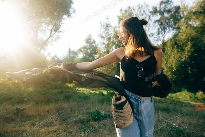 Стильный хипстер девушка позирует в солнечном парке с удивительными солнечными лучами