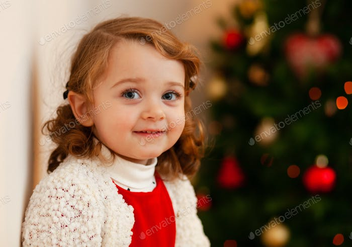 Beautiful little child near Christmas tree.