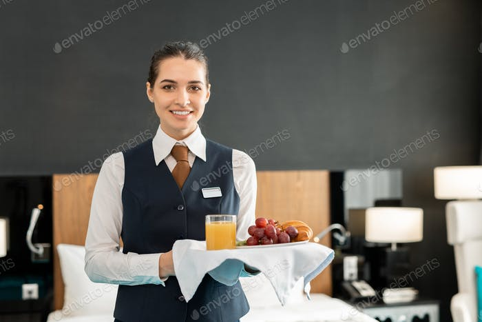 Young smiling hotel staff holding tray with breakfast