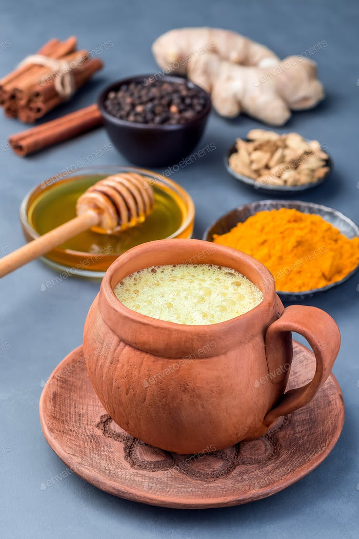 Yellow moon milk with turmeric in clay cup, ingredients on background, vertical