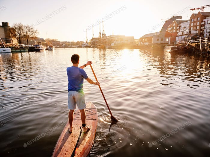 Man standing on paddleboard on river at dawn, shot from behind