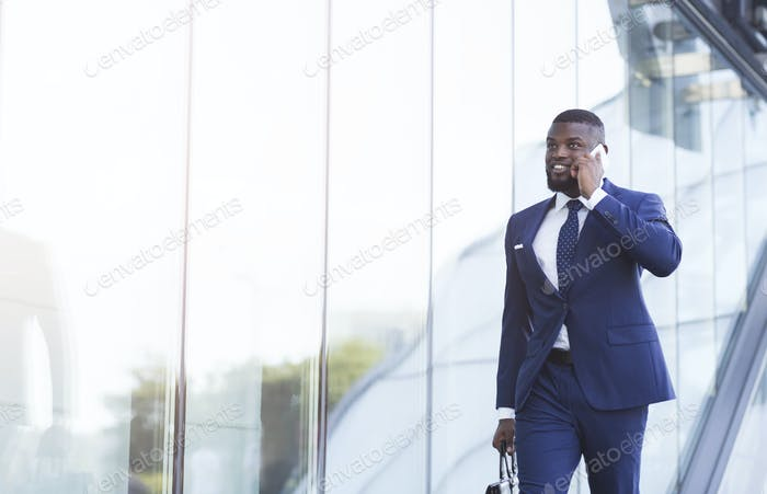 Cheerful Black Businessman Having Phone Conversation Walking In Urban Area