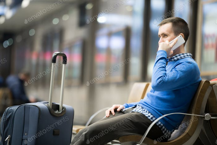 Young traveler with suitcase and phone