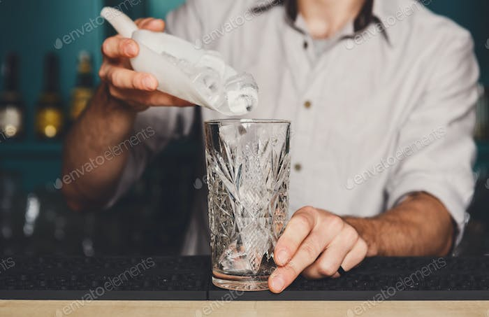 Barman's hands pouring ice for cocktail