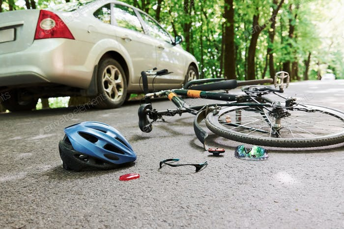 Danger place. Bicycle and silver colored car accident on the road at forest at daytime