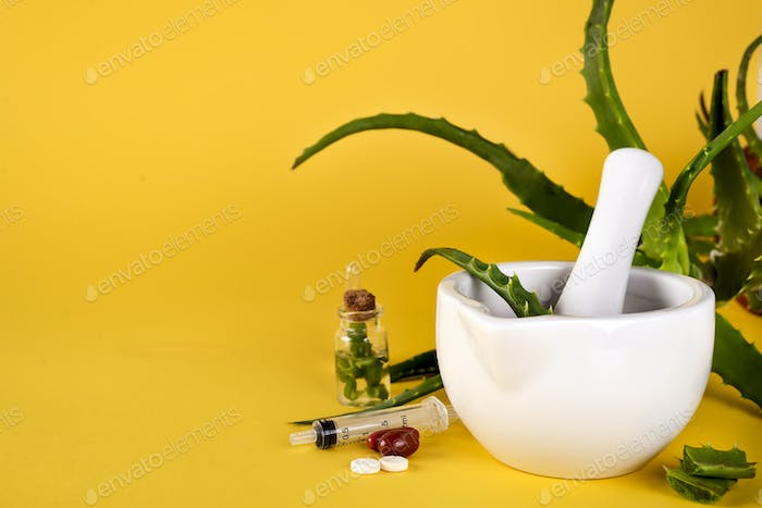Aloe vera leaf, white mortar full of chopped aloe and bottles of aloe gel or infusion.