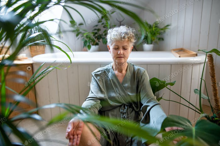 Senior woman doing yoga in bathroom at home, relax and self-care concept