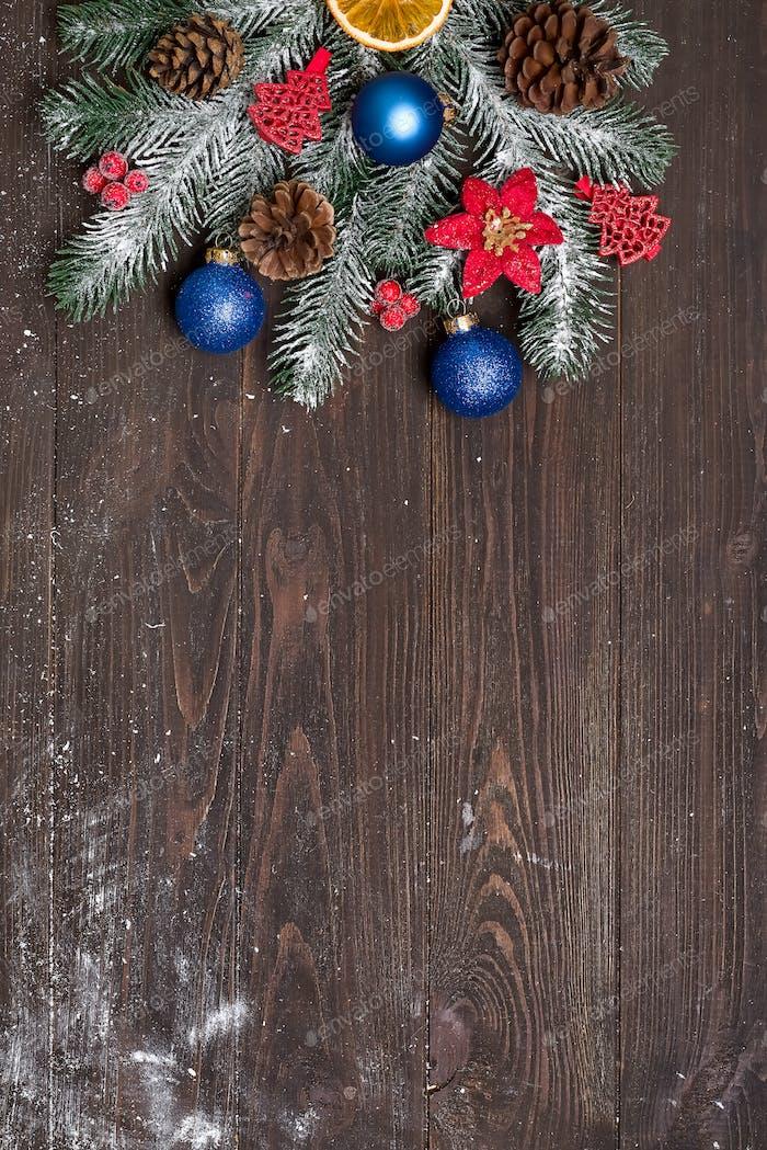 Weihnachts-Grußkarte mit Dekor und Tannenzweig auf dunklem Holzhintergrund. Draufsicht mit