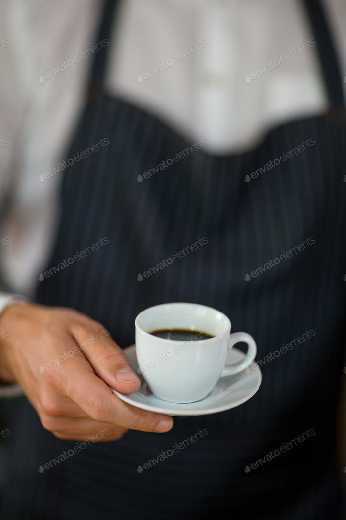 Mid-section of waiter standing with cup of coffee