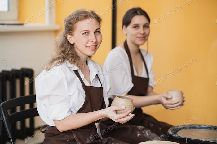Die weiblichen Töpfer machten eine Tonvase fertig, um sie vom Töpferrad zu entfernen. Erstellen einer Vase