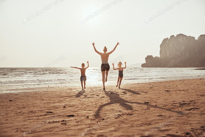 Mother and her children skipping along a sandy beach together