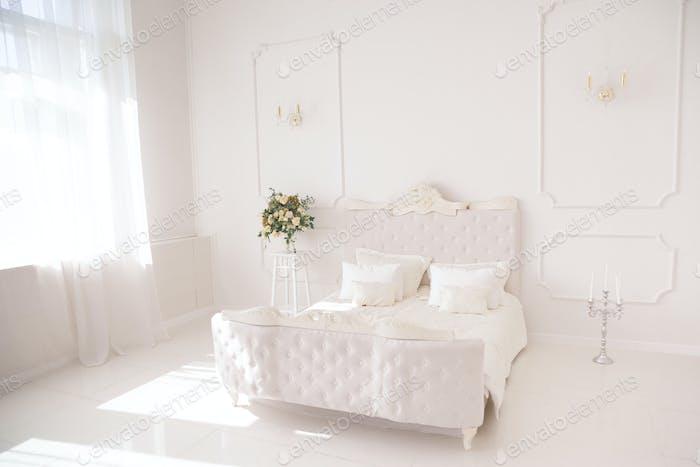 Schlafzimmer in weichen hellen Farben. großes komfortables Doppelbett im eleganten klassischen Schlafzimmer