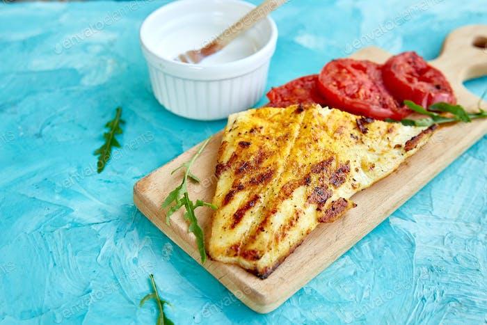 Gegrilltes Hechtfilet mit Tomaten auf Holzbrett