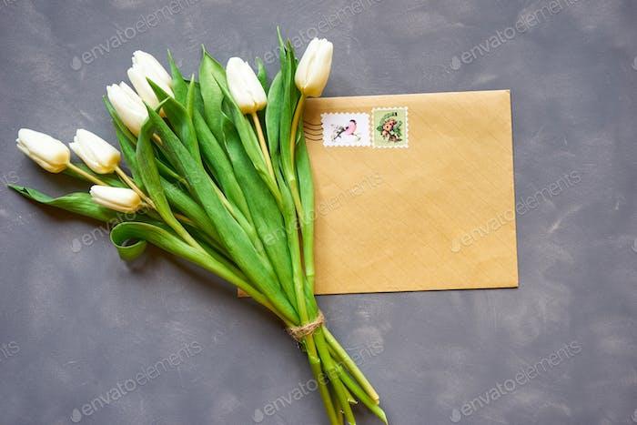 Weiße Tulpen Blumenstrauß und Postkarte auf grauem Hintergrund