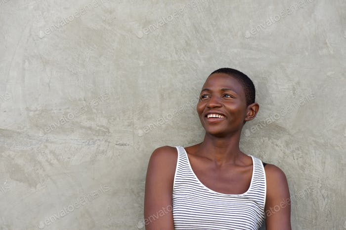 laughing beautiful black woman leaning against wall