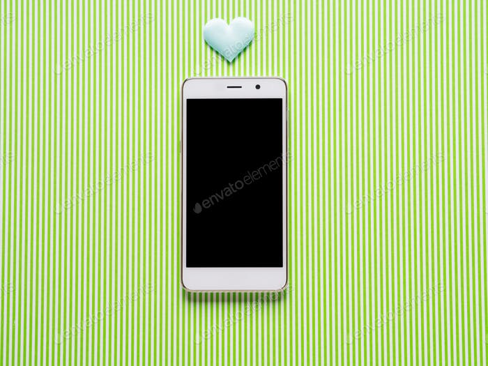 Heart and smartphone on green background