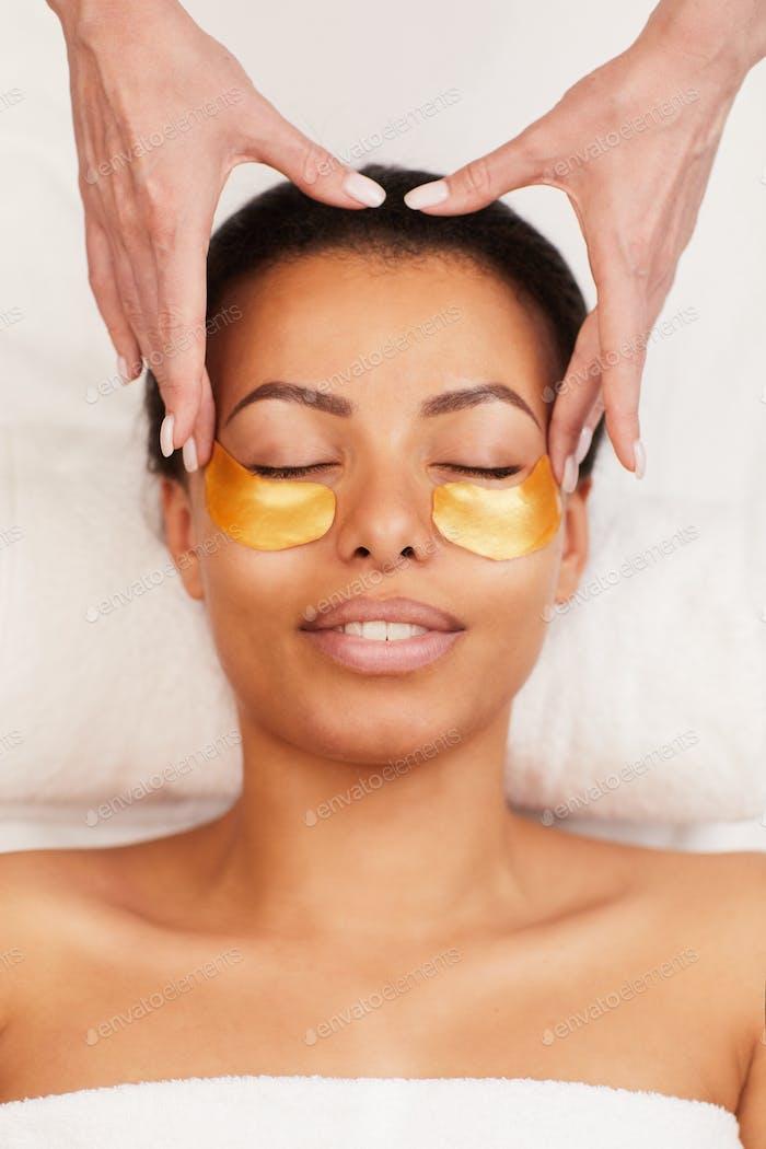 Young Woman Enjoying Facial Care in Spa