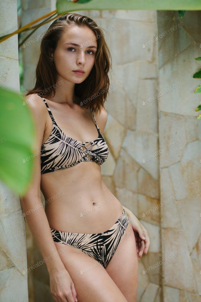 young adult female in bikini near stone wall