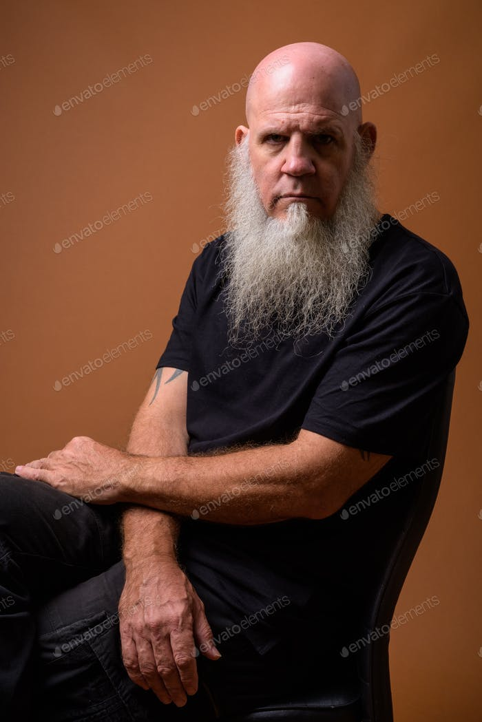 Reife Glatze Mann mit langen grauen Bart vor braunem Hintergrund
